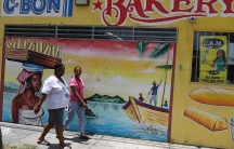 Women walk past a mural in the Little Haiti neighborhood in Miami, May 17, 2017.