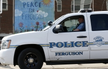 A Ferguson Police officer drives past a mural in Ferguson, Missouri, on March 12, 2015.
