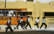 A Malaysian school boy walks past a street mural depicting a school bus and students.