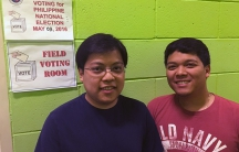 Brothers stand in front of polling place signs, against green wall
