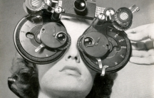 Woman looks through a phoropter in 1945.
