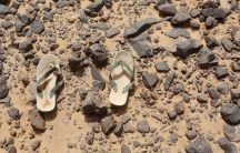 A pair of flip flops, left behind by a migrant, lies on the ground in the Sahara Desert near the border of Algeria and Libya.
