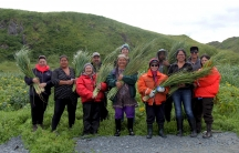 a group of people in a field holding traditional grass baskets