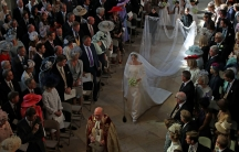 A bride, Meghan Markle, walks down the center of the aisle of a church. Her long white train drags beside her. Around her, everyone is standing.