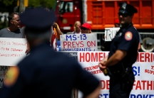 Police stand along barricades while protesters hold signs about the MS-13 gang.