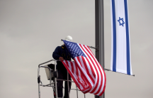 A worker on a crane hangs a US flag next to an Israeli flag, next to the entrance to the US consulate in Jerusalem, May 7, 2018.