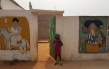 A little girl looks into a vodun convent in Togo.