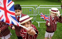 Schoolchildren wave British flags in a garden just days before the next royal wedding.