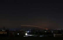 Missile fire is seen in a yellow streak across the night sky over Daraa, Syria.