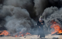 A Palestinian demonstrator walks with black smoke and tires burning in the background.