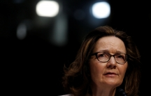 CIA Director nominee Gina Haspel, wearing dark rimmed glasses, looks right in the medium cropped portrait.