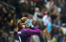 Stephanie Labbe raises her hands while standing in goal.