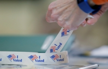 FILE PHOTO: A voter peels off an
