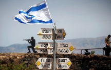 An Israeli soldier stands next to signs pointing out distances to different cities, on Mount Bental, an observation post in the Israeli-occupied Golan Heights that overlooks the Syrian side of the Quneitra crossing, Israel May 10, 2018.