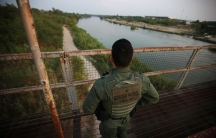 Agent in uniform stands on bridge looking over green river