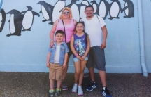 Photo of a photo of family in front of wall with penguins painted on it
