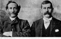 black and white photo of two men sitting next two each other