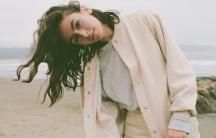 a woman with dark hair on a beach