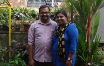 Sujitha (right) and her husband Manu (left) stand in the center of the frame in a portrait photograph.