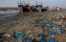 blue plastic bags wash up on a beach in Vietnam