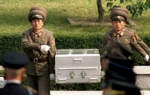 North Korean soldiers carry a coffin believed to contain the remains of a US soldier to the border with South Korea during repatriation ceremonies at the truce village of Panmunjom, South Korea, October 9, 1998.
