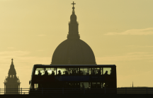 a bus carries commuters as it travels over Waterloo Bridge in London
