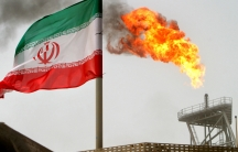 A gas flare is seen in the background with the Iranian flag flying in the wind in the foreground.