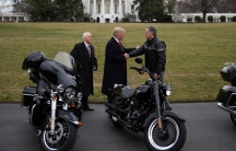 US President Donald Trump shakes hands with Matthew Levatich, CEO of Harley-Davidson, accompanied by Vice President Mike Pence in a picture with two motorcycles in the foreground and the White House in the background.