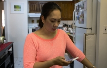 Close-up of woman in kitchen, looking at phone