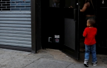 Young boy entering building from sidewalk