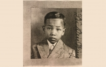 sepia toned image of young boy, with some damage to photo around edges