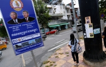 A blue sign showing two politicians stands next to an intersection in a city, where a woman is waiting to cross the street. The signs are written in Cambodian.