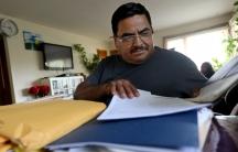 Man sits behind large stack of papers, brown envelopes