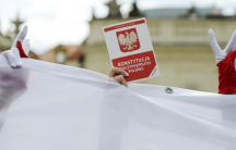 A demonstrator holds a copy of the Polish Constitution