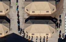 separated migrant children walk in a tent camp in texas