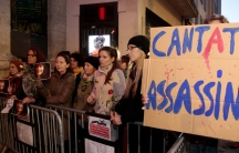 A crowd stands behind a metal gate. One holds a sign that says