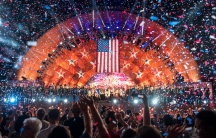 A crowd watches an illuminated bandshell decorated with red and blue stars while confetti falls in the air.