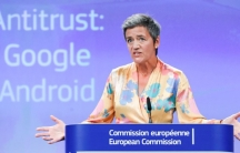 European Competition Commissioner Margrethe Vestager stands at a podium with a screen behind her reading