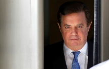 In this close-up photograph, former Trump campaign manager Paul Manafort is seen walking out of the US District Court in Washington DC, dressed in a suit with a blue tie.