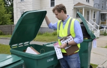 Cody Marshall, with The Recycling Partnership, looks through a recycling bin in Lynn, Massachusetts. His organization is working with cities across the nation, helping them educate residents on how to recycle better.
