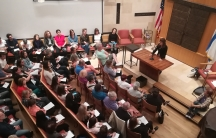 Overhead view of congregation in pews, while woman stands at podium speaking