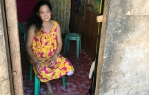 a woman with her left leg amputated at the knee sits in a doorway
