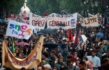 French civil servants and students carry labor union flags and banners as they march in protest during a national day of strikes by public sector workers, in Paris, France, May 22