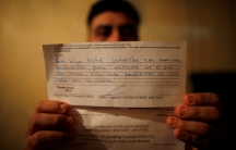Letter from US government in focus, being held up by a man who is out of focus behind it