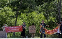 People stand on side of road in front of trees holding signs; one reads