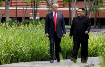 President Donald Trump and North Korea's leader Kim Jong-un walk together before their working lunch during their summit at the Capella Hotel on the resort island of Sentosa, Singapore on June 12, 2018.
