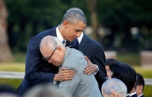 An older Japanese man hugs former President Barack Obama