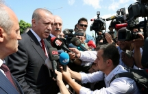 A crowd of reporters surrounds Turkish President Tayyip Erdoğan