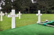 Two white crosses engraved with names sit in a cemetary