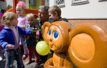 A man poses with small children next to a wooden image of the cartoon character Chebrashka.